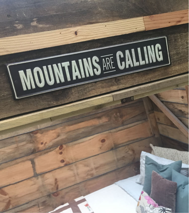 Wall mounted art that says Mountains are calling