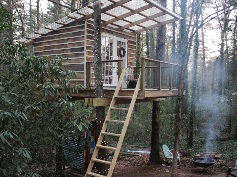 Exterior shot of treehouse with a fire burning in the fire pit