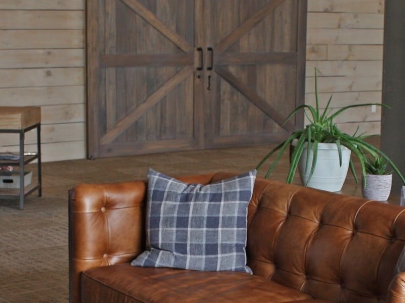 Interior shot of a leather couch and wood floor and wall