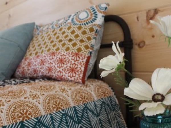 Interior shot of flowers next to a bed