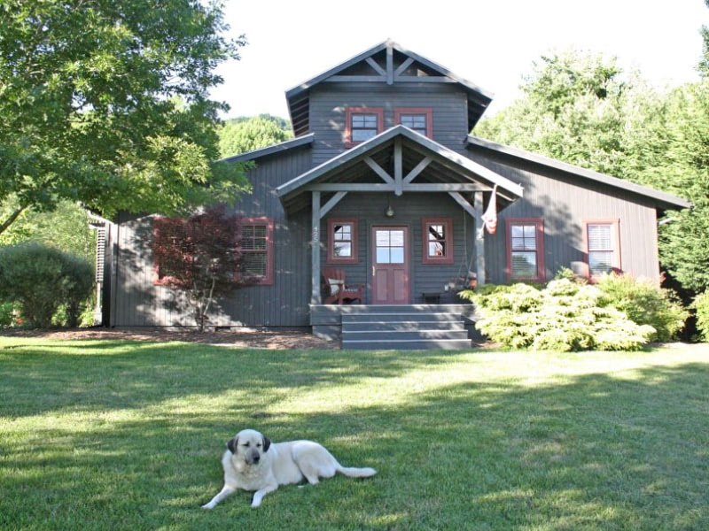 Exterior of Tuka Loop home with a dog in the front yard